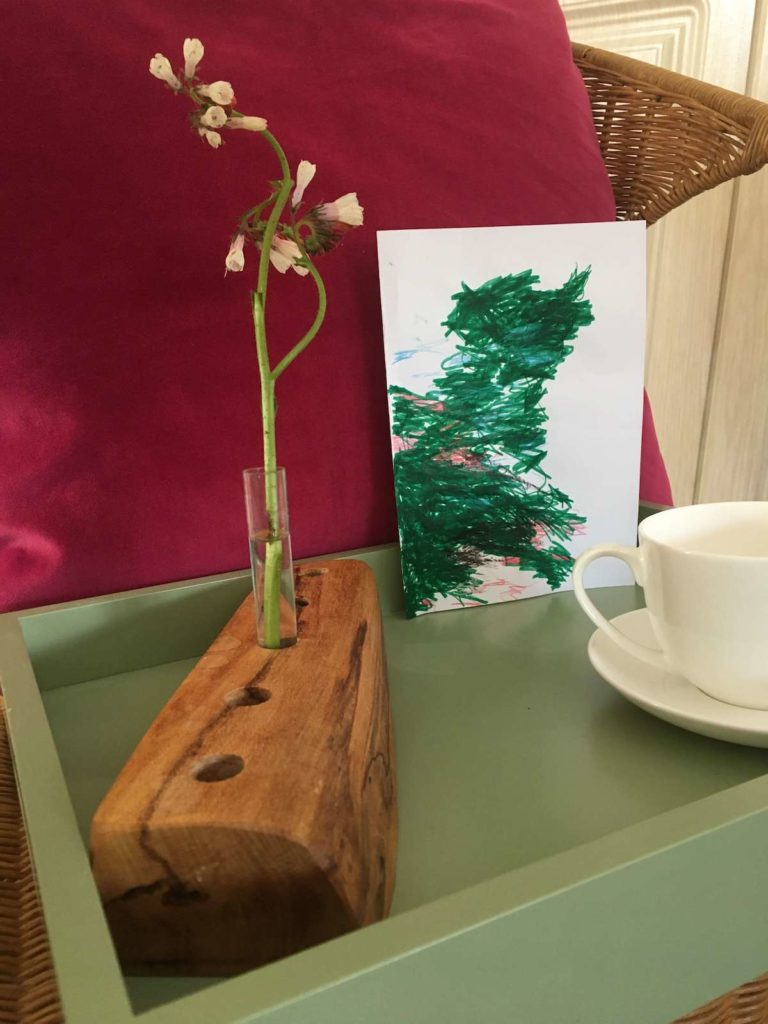 Wooden holder with flower and cup beside